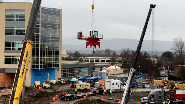 The crane's cab is lifted into the air by a smaller crane.